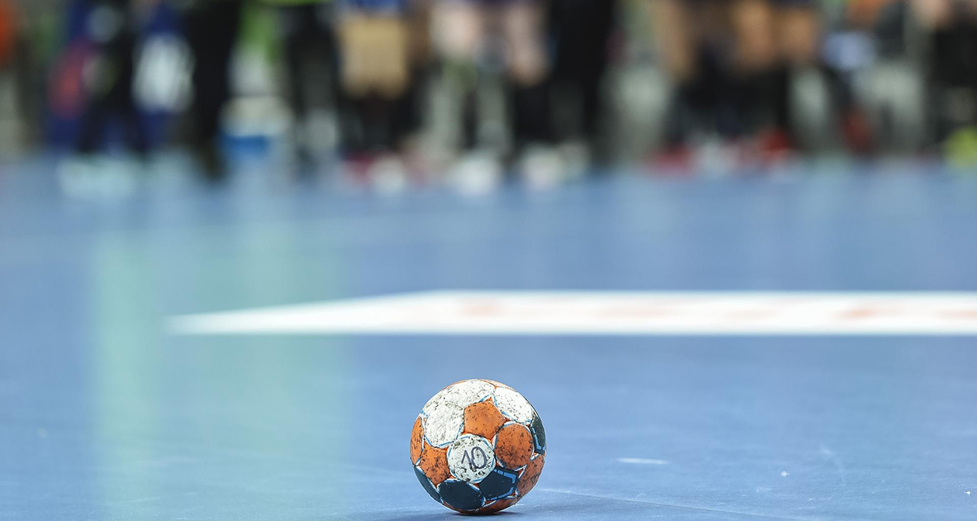 Handball ball lying on the blue parquet .